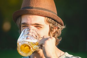 Young man drinking beer from the cup