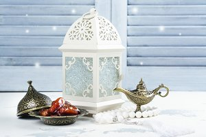 Arabic lantern, dates, aladdin lamp and rosary on white background