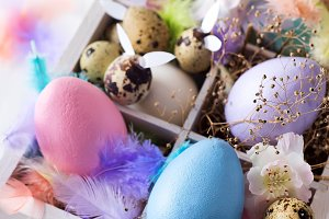Colorful easter eggs in wooden box on white