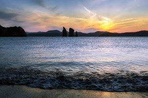 Beautiful sunset over rocks in sea