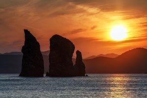 Scenery sunset over rocks in ocean