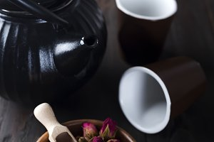 Rose buds tea on wooden bowl with tea pot