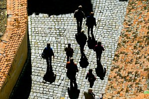 people walking cobblestone street