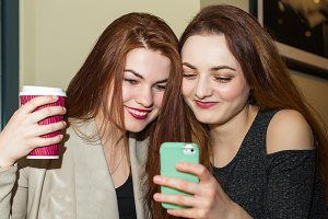 Girl showing mobile phone to a friend