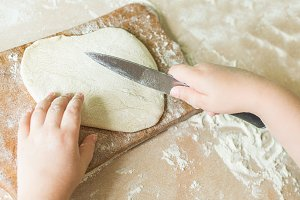 A child cuts the raw dough
