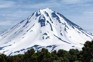Snowy cone of volcano at sunny day
