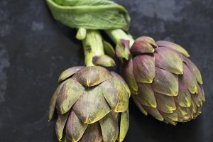 Two fresh artichokes on a dark table