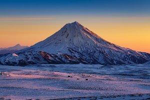 Snowcapped cone volcano at sunrise