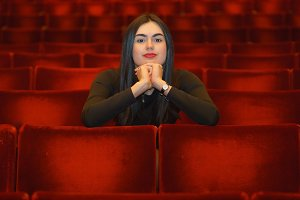 Brunette girl with hands under her face sitting in the empty red theater hall