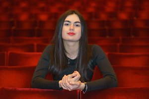 Brunette young woman sitting in the empty red theater hall