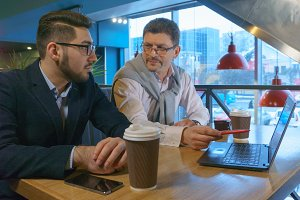 Two coworkers adult man in glasses and his young partner discusses a project with a laptop in a cafe