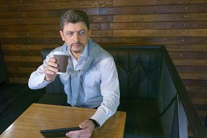 Man mature work with tablet and drinks coffee in cafe