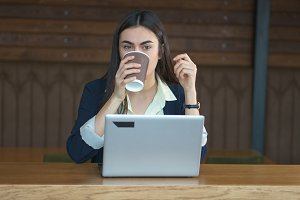 Cute brunette girl working at a laptop and drinking coffee
