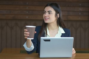 Brunette girl with a laptop and coffee working in cafe in coffee break
