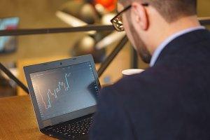Man in glasses watches the rising exchange chart on the laptop