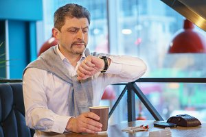 Man mature in a white shirt with sweater looks at their watch holds morning coffee