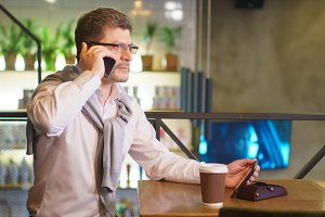Mature handsome businessman in eyeglasses with tablet speaks on the phone in cafe