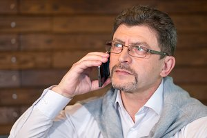 Man mature in eyeglasses and white shirt with sweater speaks on the phone in a cafe
