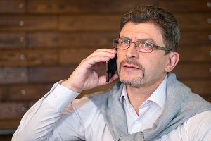 Mature man in eyeglasses and white shirt with sweater speaks on the phone in a cafe