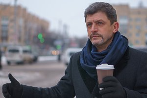 Mature man in a coat and scarf holding coffee trying to take a taxi