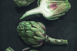 Artichokes on a dark textured table