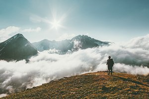 Traveler hiking in mountains clouds