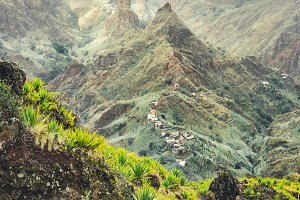 Mountain peaks of Xo-Xo valley in sun light. Local village in the valley. Many agava plants grow on the steep stony slopes. Santa Antao island, Cape Verde