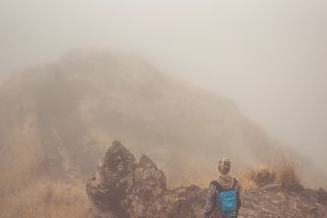 Woman hiker on the cobbled misty path on the mountain crest on Santo Antao island, Cape Verde