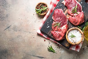 Raw beef steak with herbs on stone table. Top view.