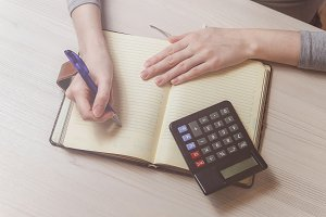 Woman hands writing on book in office. Business woman working on desk of wood