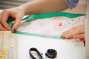 Seamstress hands on the work table with pattern and measuring tape