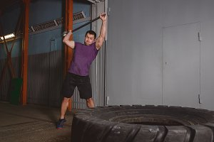 Sport Fitness Man Hitting Wheel Tire With Hammer Sledge Crossfit Training, Young Healthy Guy Gym Interior.