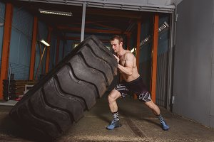 crossfit sport training concept - man flipping tire.