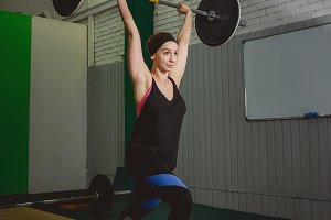 Strong woman lifting barbell as a part of cross exercise routine