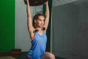 Muscular young fitness woman lifting a weight in the gym.