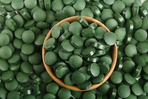 heap of Spirulina tablets algae nutritional supplement in wooden bowl as a background close up top view. Flat lay