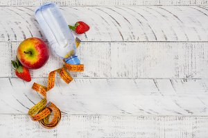 Apple, bottle of water and measuring tape on white background