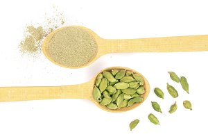 Green cardamom seeds and powder in a wooden spoon isolated on white background. Top view. lay flat