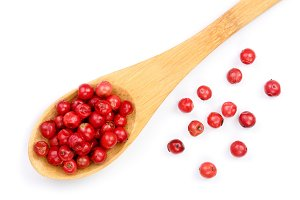 pink peppercorns seeds in wooden spoon isolated on white background. Top view. Flat lay