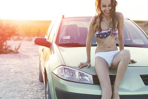 beautiful sexual woman sits on the car at sunset