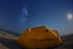 orange tent on the beach at night under the starry sky