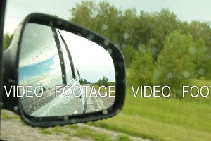 Reflection of side-view mirror of car driving in the countryside on rainy day