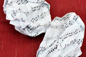crumpled sheet music on red
