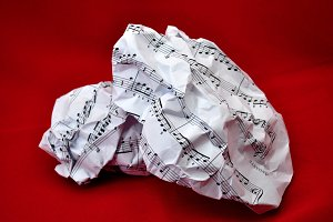 Crumpled sheet music lying on red
