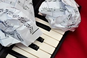 Crumpled sheet music lying and piano