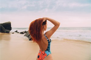 young red-haired woman admiring the ocean, view from the back