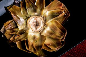 Boiled artichoke on a dark plate