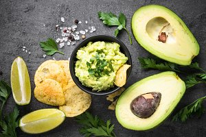 Traditional latinamerican mexican sauce guacamole and chips on b