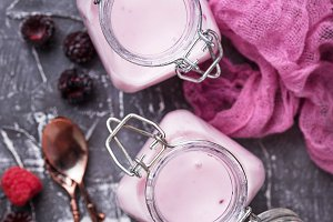 Sweet yogurt with berry in a glass jars
