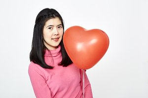 Woman holding red heart shaped